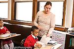K-8 Parochial School Bronx New York Grade 4 female teacher holding workbook and talking to male student horizontal