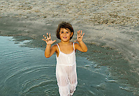 Girl playing in a beach puddle.