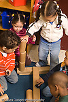 Preschool classroom New York City group of 3 year olds boys and girls working cooperatively building with blocks vertical