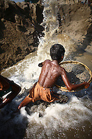 A child works with a sieve at Bhollar Ghat. At least 10,000 people, including 2,500 women and over 1,000 children, are engaged in stone and sand collection from the Bhollar Ghat on the banks of the Piyain river. Building materials such as stone and sand, and the cement which is made from it, are in short supply in Bangladesh, and commands a high price from building contractors. The average income is around 150 taka (less than 2 USD) a day.