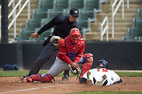 Lakewood BlueClaws catcher Gregori Rivero (23) fields a throw as Michael Hickman (18) of the Kannapolis Intimidators slides into home plate as umpire Dillon Wilson prepares to make the call at Kannapolis Intimidators Stadium on April 8, 2018 in Kannapolis, North Carolina.  The Intimidators defeated the BlueClaws 5-1 in game one of a double-header.  (Brian Westerholt/Four Seam Images)
