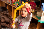 Preschool Headstart 3-5 year olds girl talking and making construction from colorful plastic tubes horizontal