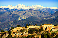 Ancient construction under golden sunset light with snow-capped Prealps mountains in the background, above Nice, French Riviera (Côte d'Azur), France