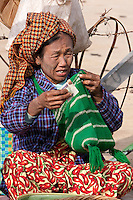 Myanmar, Burma.  Woman of Pa-O Ethnic Group at Local Market, Inle Lake, Shan State, Taking Money from her Money Pouch.  She has remnants of thanaka paste on her face, a natural cosmetic sunscreen.
