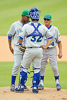 Lexington Legends pitching coach Jerry Nyman (24) has a meeting on the mound with pitcher Miguel Almonte (27) and catcher Jin-Ho Shin (32) during the South Atlantic League game against the Kannapolis Intimidators at CMC-Northeast Stadium on July 31, 2013 in Kannapolis, North Carolina.  The Intimidators defeated the Legends 3-2.  (Brian Westerholt/Four Seam Images)