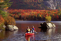 AJ1013, Vermont, canoe, canoeing, Mother and daughter paddling a red canoe on a fall day on Marshfield Pond in Marshfield. Mad River Canoe Products.