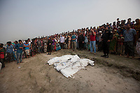 Bangladeshi people gather around the dead bodies recovered from the Padma River after a ferry capsized in the River Padma  after being hit by a cargo vessel at Paturia , in Manikganj district, about 80 kilometers northwest of Dhaka, Bangladesh, Monday, Feb. 23, 2015