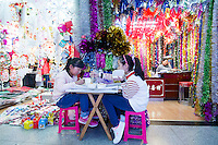 November 27, 2015, Yiwu China - Two young sisters eat lunch in front of booths displaying Christmas decorations inside the Festival Arts section of the Yiwu International Trade Market. Yiwu International Trade Market is the world's largest whole sale market for small commodities. Christmas decorations are available for bulk purchase all the year round.v