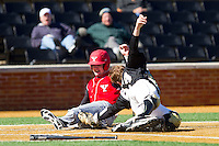 Devin Higgins (6) of the Youngstown State Penguins slides into home plate ahead of the tag from Garrett Kelly (28) of the Wake Forest Demon Deacons at Wake Forest Baseball Park on February 24, 2013 in Winston-Salem, North Carolina.  The Demon Deacons defeated the Penguins 6-5.  (Brian Westerholt/Four Seam Images)