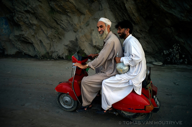 Two men on a red scooter smile as the drive along the Swat river in Mingora, Swat valley, Pakistan, on Aug. 21, 2010.