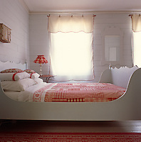 The sleigh bed in the master bedroom has been painted a pale grey and teamed with red and white bed linen and simple blinds with red piping