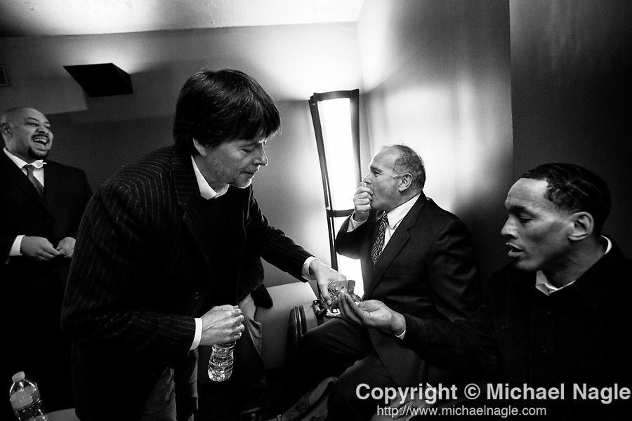 Filmmaker Ken Burns shares candies with Raymond Santana, left, Jim Dwyer, columnist for The New York Times, center, and Korey Wise, right, backstage at the SVA Theatre before the New York premiere of Burns' Central Park Five documentary on November 15, 2012.  Antron McCray, Raymond Santana, Kevin Richardson, Yusef Salaam, and Korey Wise, all of whom served prison sentences after being wrongly convicted in the Central Park jogger case, had their convictions vacated in 2002, after the confession of Mathias Reyes, who was already serving a life sentence for rape and murder.  Reyes' DNA linked him to the crime.  Photograph by Michael Nagle