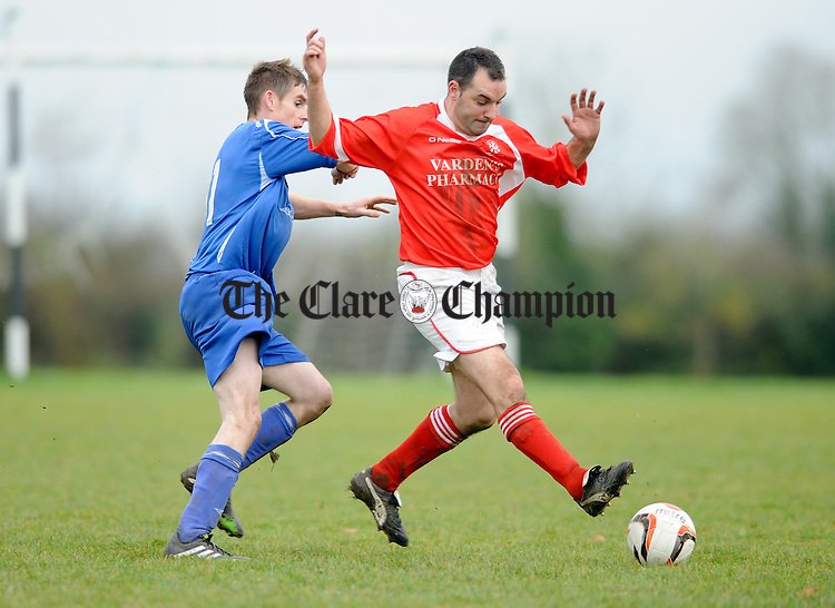 Gary Collins of Ennis Town in action against Seamus Lawlor of Newmarket Celtic during their game in Newmarket. Photograph by John Kelly.