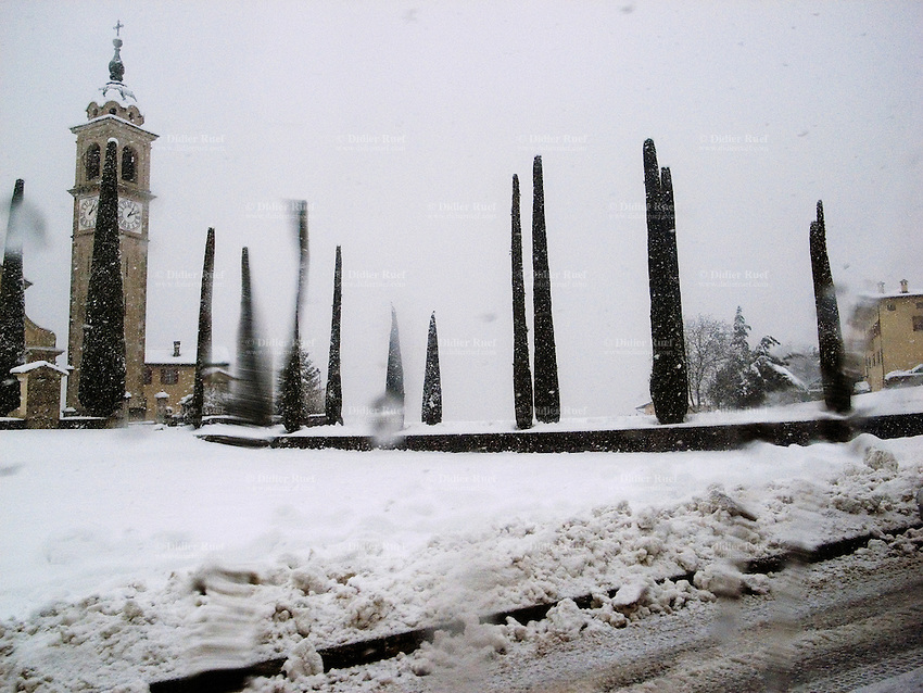 Switzerland. Canton Ticino. Gentilino. Sant'Abbondio church. Catholic church and the Holy Cross. Bell tower and a row of cypress trees. Snow storm in winter. Gentilino is 10 km outside Lugano. 02.02.09 © 2009 Didier Ruef