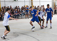 Santa Cruz, Brazil - July 7, 2014: A local private school Centro de Integracao Objectivo holds futsol games. Players of all ages play with school members surrounding the covered field to watch and cheer. In this game, two Americans joined the team in blue for their game.