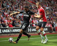 (L-R) Jordan Ayew of Swansea City against Jack Stephens of Southampton during the Premier League match between Southampton and Swansea City at the St Mary's Stadium, Southampton, England, UK. Saturday 12 August 2017