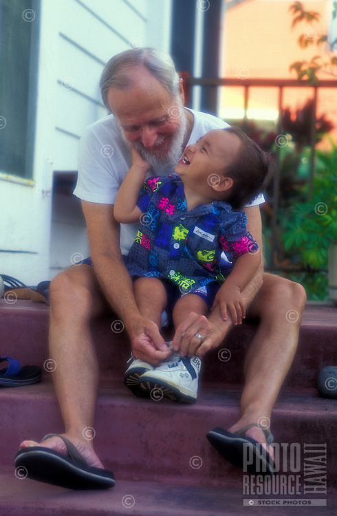 Portrait of a grandfather tying the shoes of his part Hawaiian grandson.
