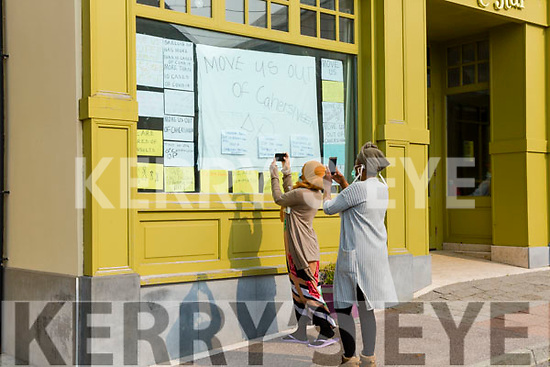 Two residents of the Skellig Star Direct Provision Centre in Cahersiveen on Saturday after the announcement that there were further cases of Covid-19 in the Centre take pictures of the front window of the hotel.