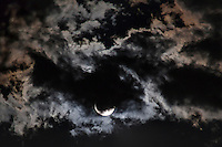 The second full moon of July 2015, the Blue Moon, hides behind passing clouds and makes them  shine in the night.