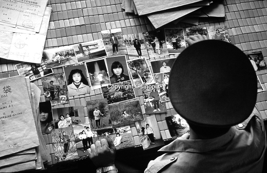 Zhu Wenguang, an  ex-policeman, looks at a photographs of women that have been stolen and kidnapped in China.  Zhu helps families who have lost wives and daughters to the kidnapping gangs and attemtps to save them. He has saved more than eighty people from virtual slavery in the past seven years. Theft of women and girls is oncreasing as the gender gap widens.<br /> 2002<br /> <br /> photo by Richard Jones / Sinopix