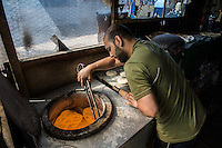 Calais 8-4-16 Scene in the Jungle Camp populated by refugees and migrants hoping to get to Britain. Afghan man baking bread.