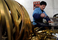 A worker cuts copper strips to size at the Shanghai General Harmonica Factory (SGHF) in Shanghai, China. Although it makes well-respected brands such as the Huang, Suzuki, and Hohner harmonicas that are favored by many professional musicians around the world, the 60 years old state owned SGHF had to trim down its work force from 800 in the mid 1980's to just over 100 today..23-FEB-04