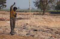 Rajasthan, India.  Worker Using Long Rod to Stir Wood Shavings into the Underground Brick Furnace.