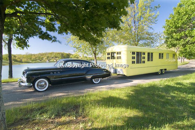 1949 black Buick Eight Roadmaster pulling a yellow 1953 Vagabond vintage travel trailer.