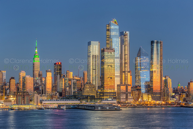 The mixed-use Hudson Yards real estate development and other buildings on the West Side of Manhattan in New York City.  The orange colored western sky adds beautiful reflections to the windows of the skyscrapers at twilight.