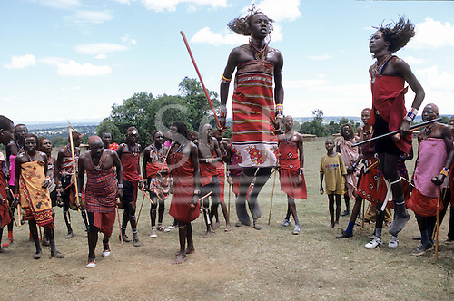 Lolgorian, Kenya. Siria Maasai Manyatta; group of moran doing their traditional 'ipid' jumping dance.