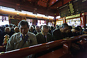 Japanese businessmen and women pray for a successful 2015