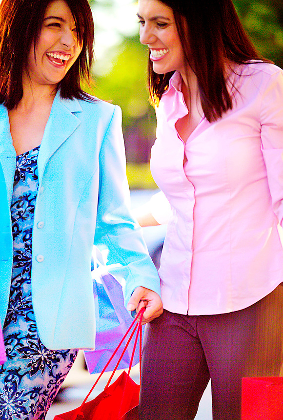 Two females shopping and carrying brightly colored shopping bags.