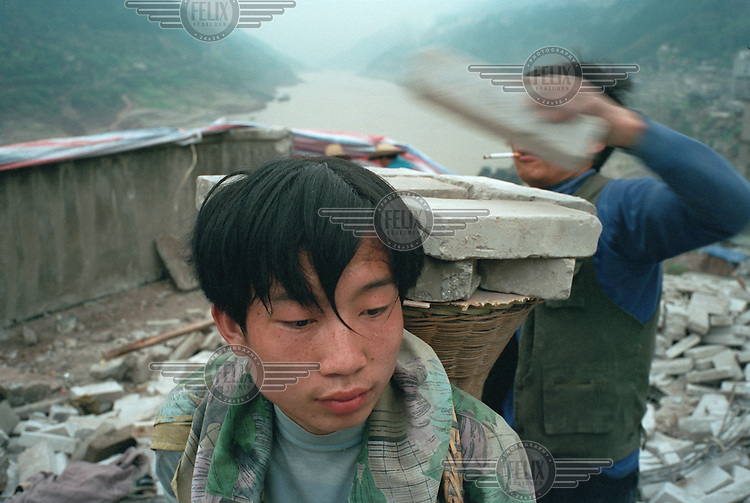 Migrant workers from surrounding villages dismantle a recently vacated building.  Houses in towns along the Yangtze river are being demolished to make way for the Three Gorges Dam project, which will raise the water levels of the river and inundate lower-lying areas.  The purpose of dismantling buildings in the city is to clear an area and to prevent relocated families from returning to their old houses.