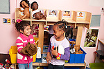 Education Preschool 3-4 year olds two girls talking and playing in pretend play area using puppets and talking