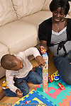 2 year old toddler boy with mother interaction playing with toys language development mother talking and involved  playing with plastic human figures and block tower African American vertical