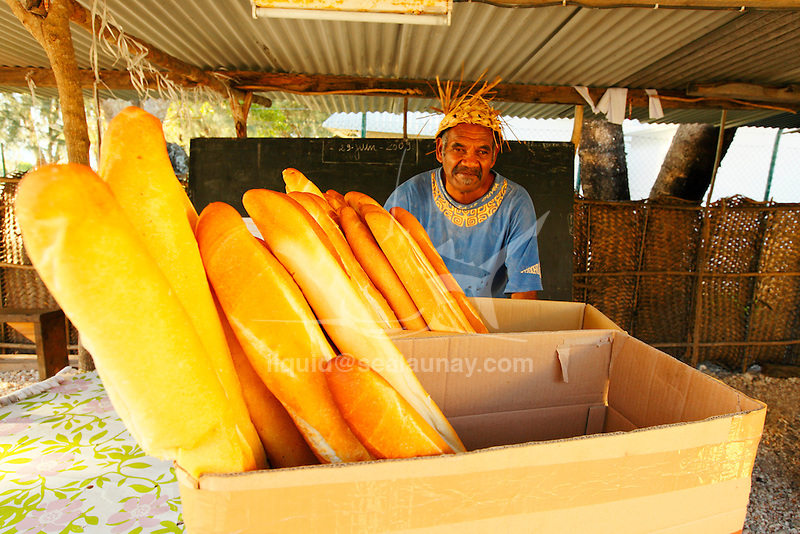 """A man selling breads in the Fayaoue village on the Ouvea island in the Loyalty islands..Ouvéa (local pronunciation: [u?ve.a]) is a commune in the Loyalty Islands Province of New Caledonia, an overseas territory of France in the Pacific Ocean. The settlement of Fayaoué [fa?jawe], on Ouvéa Island, is the administrative centre of the commune of Ouvéa..Ouvéa is made up of Ouvéa Island, the smaller Mouli Island and Faiava Island, and several islets around these three islands. All these lie among the Loyalty Islands, to the northeast of New Caledonia's mainland..Ouvéa Island is one of the Loyalty Islands, in the archipelago of New Caledonia, an overseas territory of France in the Pacific Ocean. The island is part of the commune (municipality) of Ouvéa, in the Islands Province of New Caledonia..The crescent-shaped island, which belongs to a larger atoll, is 50 km (30 miles) long and 7 km (4.5 miles) wide. It lies northeast of Grande Terre, New Caledonia's mainland..Ouvéa is home to around 3,000 people that are organized into tribes divided into Polenesian, Melanesian and Walisian by ethnic descend. The Iaai language is spoken on the island..The two native languages of Ouvéa are the Melanesian Iaai and the Polynesian Faga Uvea, which is the only Polynesian language that has taken root in New Caledonia. Speakers of Faga Uvea have fully integrated into the Kanak society, and consider themselves Kanak..Ouvéa has rich marine resources and is home to many sea turtles, species of fish, coral as well as a native parrot, the Uvea Parakeet, that can only be found on the island of Ouvéa..A large crustacaen called a """"coconut crab"""" or crabe de cocotier can also be found on the islands. The large crabs live in palm tree plantations and live solely on a diet of coconuts that they crack open with their powerful claws. They are blue in colour and can grow to several kilos in size. They are a land based species and do not venture into the ocean.."""