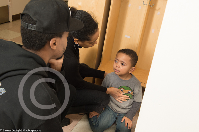 Education Preschool child care 3-3 year olds sad boy at start of day with female teacher and father, sad about separation