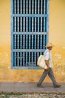 Senior man walking along a city street past a wooden grilled window, Trinidad, Cuba.