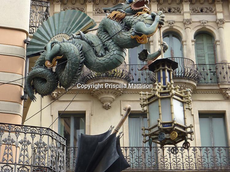 Barcelona, Spain - January 31, 2011:  A dragon holds a lantern on Casa Bruno Quadras, a former umbrella factory on Las Ramblas.