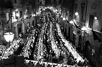 © Francesco Cito / Panos Pictures..Siena, Tuscany, Italy. The Palio. ..Each contrada (city district) holds a banquet on the evening before the race...Twice each summer, the Piazza del Campo in the medieval Tuscan town of Siena is transformed into a dirt racetrack for Il Palio, the most passionately contested horse race in the world. The race, which lasts just 90 seconds, has become intrinsic to the town's heritage since it was first run in 1597.