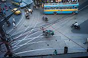 A handpulled rickshaw crosses an intersection in Kolkata, West Bengal, India.