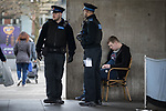 © Joel Goodman - 07973 332324 . 06/04/2017 . Manchester , UK . A man sits slumped in a chair , watched over by two PCSOs , next to Caffe Nero in Piccadilly Gardens . An epidemic of abuse of the drug spice by some of Manchester's homeless population , in plain sight , is causing users to experience psychosis and a zombie-like state and is daily being witnessed in the Piccadilly Gardens area of Manchester , drawing large resource from paramedic services in the city centre . Photo credit : Joel Goodman