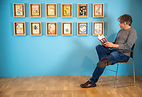 BNPS.co.uk (01202) 558833. <br /> Pic: CorinMesser/BNPS<br /> <br /> Pictured: Museum Director Adrian Green reads 'The Visitors' Book', the biography of Richard Chopping and Denis Wirth-Miller.<br /> <br /> Original artwork from the acclaimed James Bond illustrator has gone on display at a new exhibition.<br /> <br /> Richard Chopping produced the drawings for nine of the 007 book covers from 1957 to 1966.<br /> <br /> Examples of his craft, including his striking skull design for Goldfinger, are being showcased at Salisbury Museum in Wiltshire.