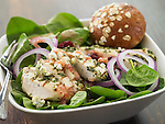 A spinach salad topped with sliced herbed chicken breast, red onion, and a whole wheat roll