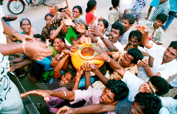People clamouring for food aid being distributed following the tsunami which struck South Asia on 26/12/2004..An underwater earthquake measuring 9 on the Richter scale triggered a series of tidal waves which caused devastation when they struck dry land. 12 countries were affected by the tsunami, with a combined death toll of over 150,000.