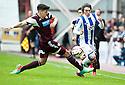 Killie's Chris Johnston is challenged by Hearts' Calum Paterson.