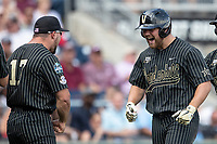Vanderbilt Commodores outfielder Stephen Scott (19) is greeted by teammate Walker Grisanti (17) after his second home run of Game 8 of the NCAA College World Series against the Mississippi State Bulldogs on June 19, 2019 at TD Ameritrade Park in Omaha, Nebraska. Vanderbilt defeated Mississippi State 6-3. (Andrew Woolley/Four Seam Images)
