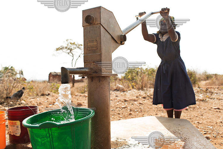 Louise Msowoya (40) collecting water from a bore hole which produces poor quality, salty water.