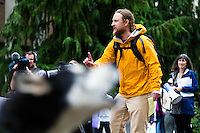 """Brett Haverstick, an activist from Idaho, speaks at a rally outside the Washington Department of Fish and Wildlife (WDFW) headquarters in Olympia, Washington against the killing of the Profanity Peak wolf pack in eastern Washington on September 1, 2016. """"Wolves and livestock cannot coexist. Livestock should be removed from federal lands if wolves are to recover in the west. You can't have both on their landscapes."""" he says. Barely visible but loudly heard, Sherman (bottom left), a 5 year-old Siberian Husky belonging to Todd Davison from Olympia, Wash.  howls into the crowd.(photo © Karen Ducey Photography)"""
