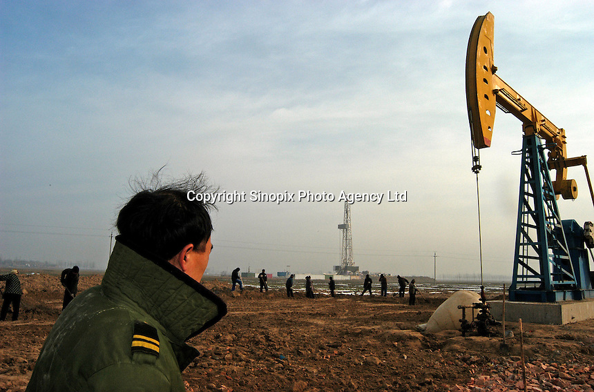 A farmer looks at the oil pump at the Sinopec Petrochemical oil field in Puyang, Henan province, China. Farmers in the area often steal natural gas for cooking and heating. They steal the gas from the pipe-line filling a big plastic bag in an hour. As soon as one finishes filling a bag, another family will fill another bag, it goes on continuously. A bag of natural gas is enough fuel for up to one week...PHOTO BY HI SHE / SINOPIX